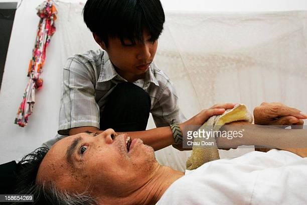 Vietnamese veteran and Agent Orange victim Nguyen Van Diem is taken care of by his only son Nguyen Van Xuan, 17. Diem was a professional soldier...