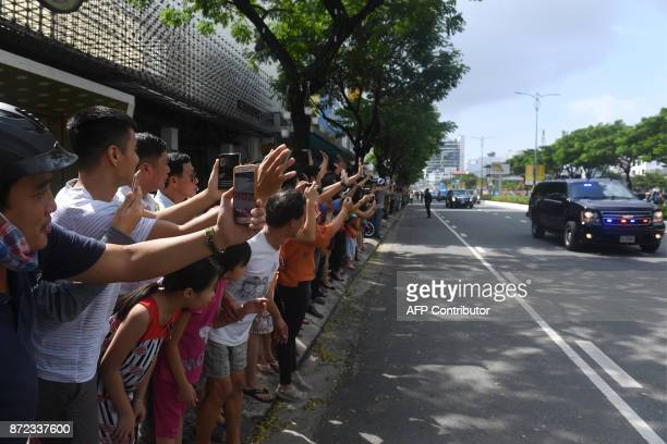 Vietnamese wave and take photos as the convoy transporting US President Donald Trump passes by after his arrival for the AsiaPacific Economic...