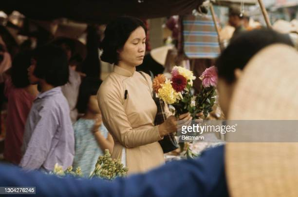 Vietnamese woman arranging flowers in a marketplace ten weeks after the Tet Offensive, in Hue, South Vietnam, 14th April 1968. The Tet Offensive was...