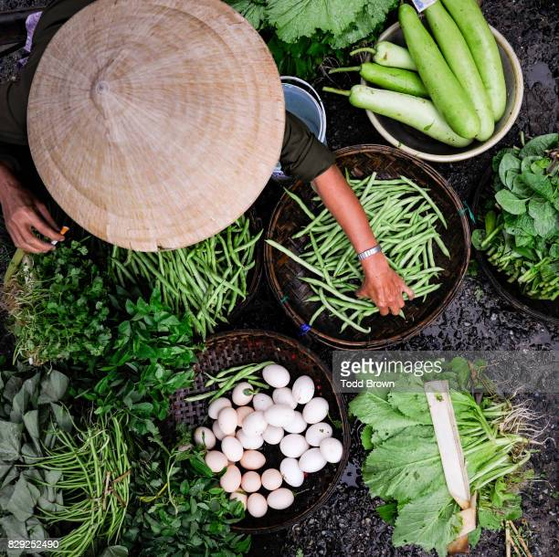 Vietnamese woman at market with vegetables from above