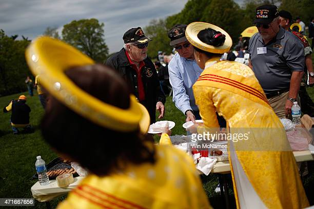 Vietnamese woman dressed in traditional clothing serve Vietnamese food to US veterans during a ceremony commemorating the 40th anniversary of the...