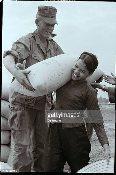 A Vietnamese woman from Cam Ne Vietnam helps marines clear out a bamboo grove by shouldering a 100 pound sack of grain | Location Cam Ne Vietnam