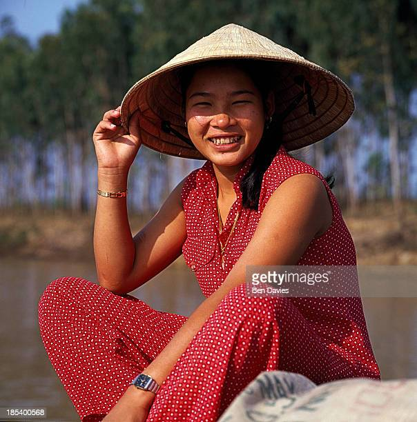 Vietnamese woman in a conical hat travels by boat along the canals in the Mekong Delta Canals are the major thoroughfares through this densely...