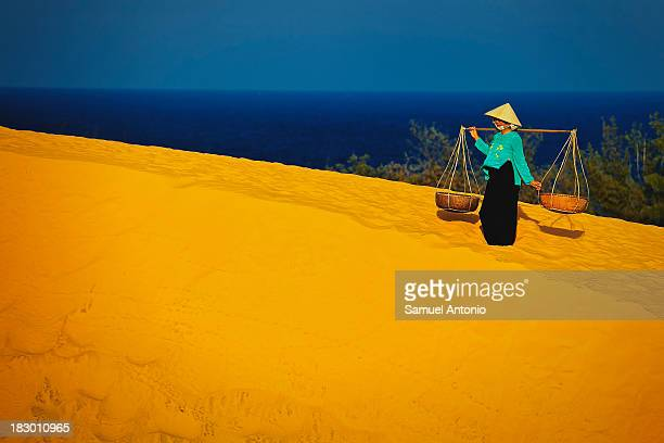 Vietnamese woman, in traditional clothing, at the Red Sand Dunes in Mui Ne, Vietnam with a view of the South China Sea in the background. Mui Ne,...