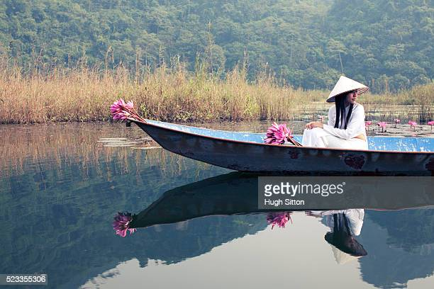 vietnamese woman in traditional dress travelling by boat - hugh sitton stock pictures, royalty-free photos & images