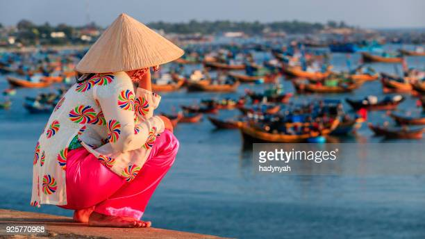 Vietnamese woman looking at fishermen's boats, Vietnam