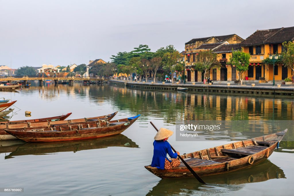 Vietnamese woman paddling in old town in Hoi An city, Vietnam : Stock Photo