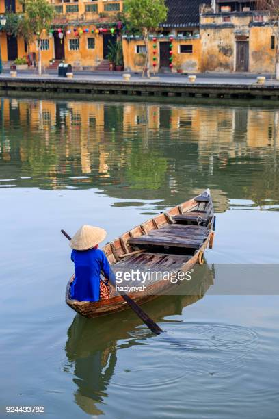 Vietnamese woman paddling in old town in Hoi An city, Vietnam