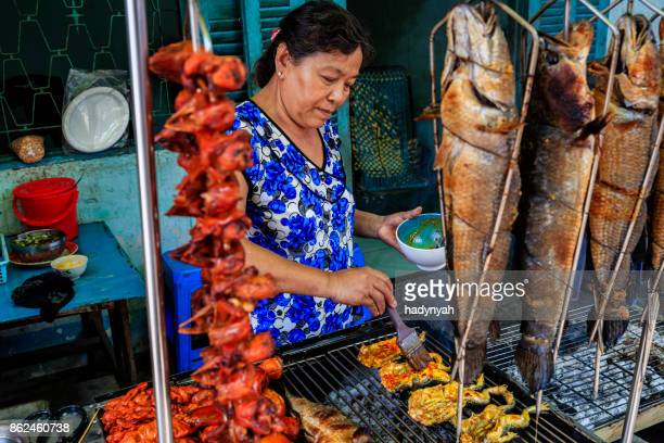 vietnamese woman preparing grilled frogs and fishes, mekong river delta, vietnam - traditionally vietnamese stock pictures, royalty-free photos & images