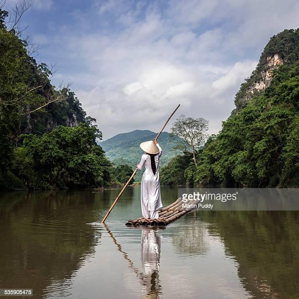 Vietnamese woman punting bamboo raft along river