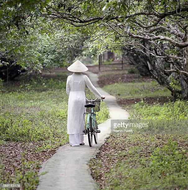 Vietnamese woman pushing bike on path