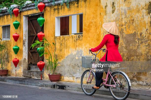 vietnamese woman riding a bicycle, old town in hoi an city, vietnam - hoi an stock pictures, royalty-free photos & images