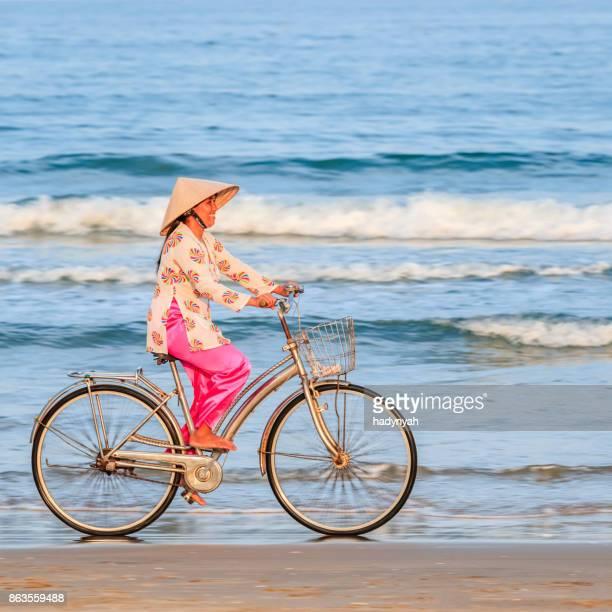 Vietnamesische Frau, die mit dem Fahrrad am Strand, Vietnam