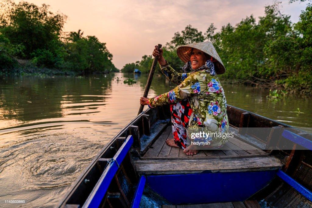 Vietnamese woman rowing a boat, Mekong River Delta, Vietnam : Stock Photo