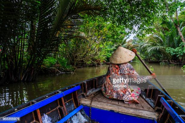 vietnamese woman rowing a boat, mekong river delta, vietnam - mekong delta stock pictures, royalty-free photos & images