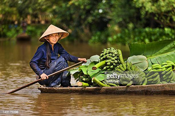 vietnamese woman rowing  boat in the mekong river delta, vietnam - traditionally vietnamese stock pictures, royalty-free photos & images