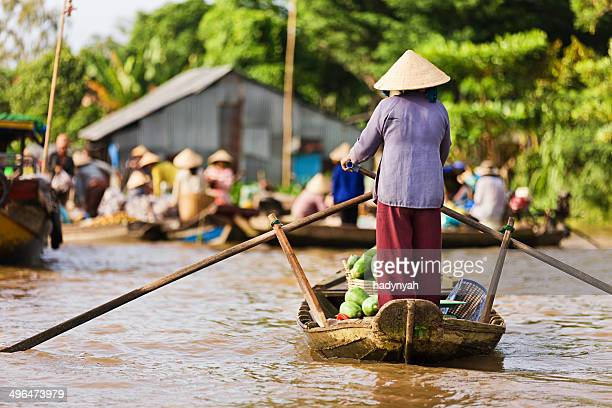 Vietnamese woman rowing  boat in the Mekong River Delta, Vietnam