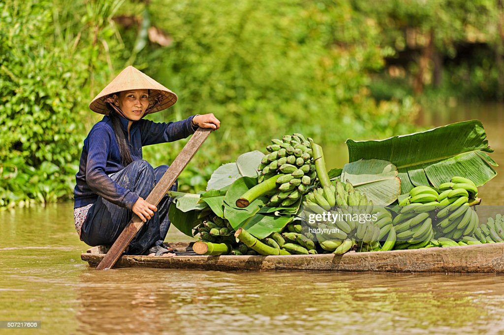 Vietnamese woman rowing  boat in the Mekong River Delta, Vietnam : Stock Photo