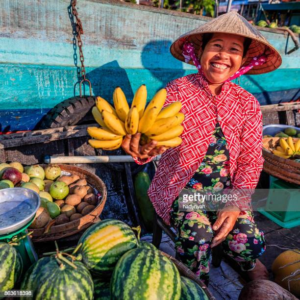 vietnamese woman selling bananas on floating market, mekong river delta, vietnam - traditionally vietnamese stock pictures, royalty-free photos & images