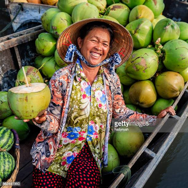 vietnamese woman selling coconuts on floating market, mekong river delta, vietnam - can tho province stock pictures, royalty-free photos & images