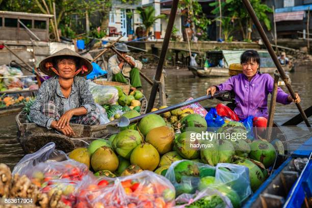 vietnamese woman selling coconuts on floating market, mekong river delta, vietnam - floating market stock photos and pictures