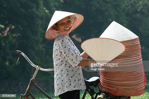 vietnamese woman selling conical hats. hanoi. vietnam. - hugh sitton stock pictures, royalty-free photos & images
