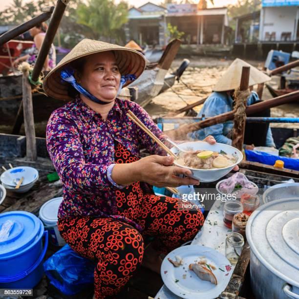 Vietnamese woman selling famous noodle soup, floating market, Mekong River Delta, Vietnam