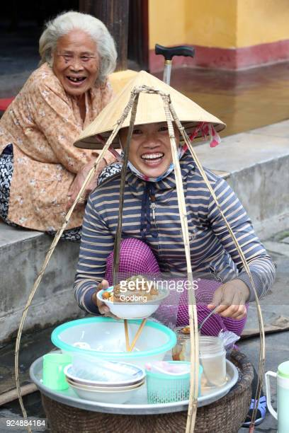 Vietnamese woman selling food in the street Hoi An Vietnam