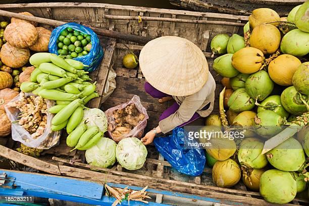 Vietnamese woman selling fruit on floating market, Mekong River Delta,