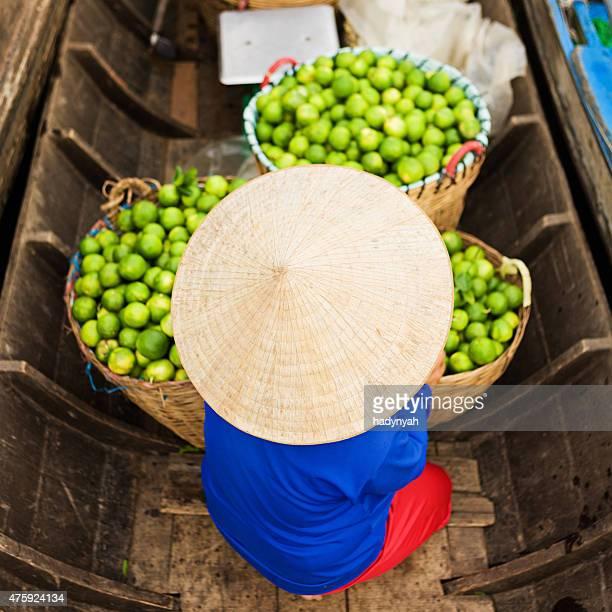 Femme vietnamienne vente de fruits frais sur le marché flottant, fleuve Mékong, Delta