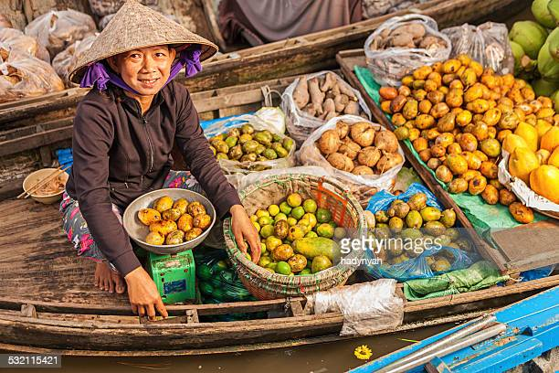 vietnamese woman selling fruit on floating market, mekong river delta, - vietnam stockfoto's en -beelden