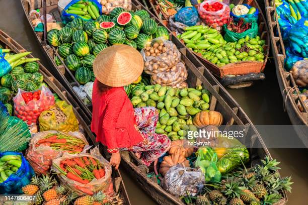 vietnamese woman selling fruits on floating market, mekong river delta, vietnam - vietnam stock pictures, royalty-free photos & images