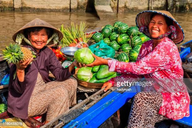 vietnamesisk kvinna som säljer frukter på flytande marknaden, mekong river delta, vietnam - vietnam bildbanksfoton och bilder