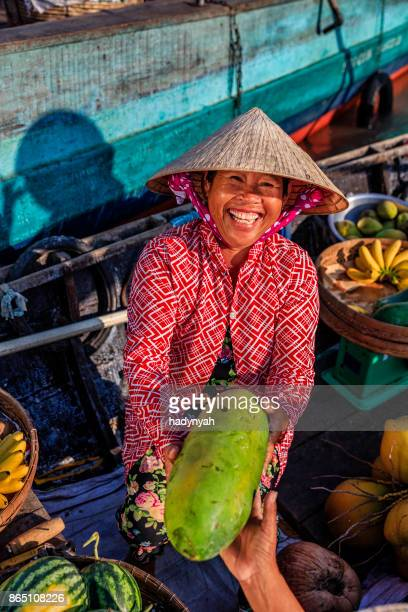 Vietnamese woman selling fruits on floating market, Mekong River Delta, Vietnam