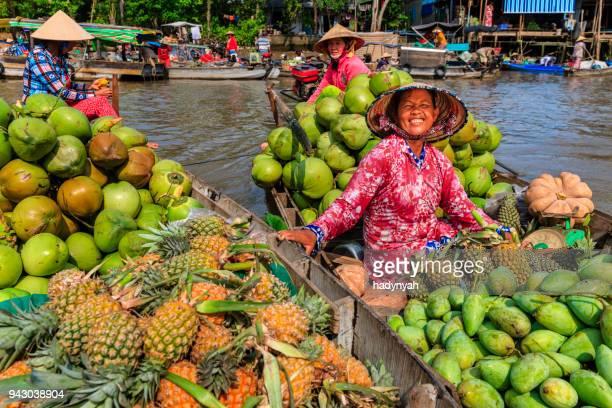 Vietnamese vrouw verkoop van vruchten op de drijvende markt, Mekong River Delta, Vietnam