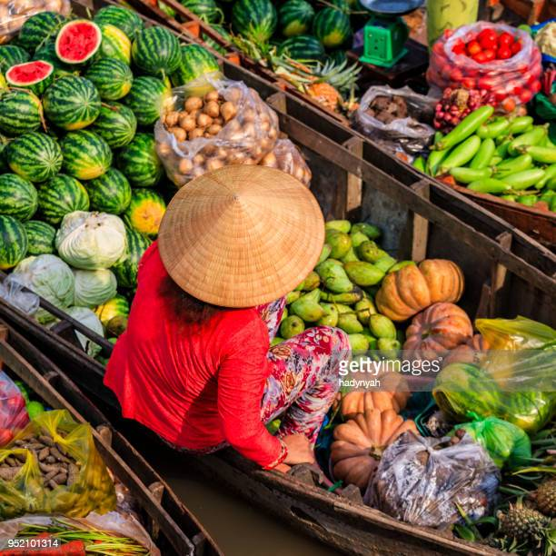 Vietnamese woman selling fruits on floating market, Mekong River Delta, Vietnam