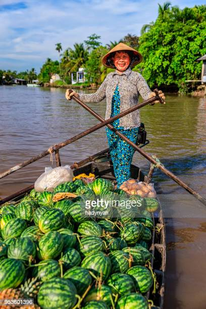 vietnamese woman selling fruits on floating market, mekong river delta, vietnam - asian style conical hat stock pictures, royalty-free photos & images