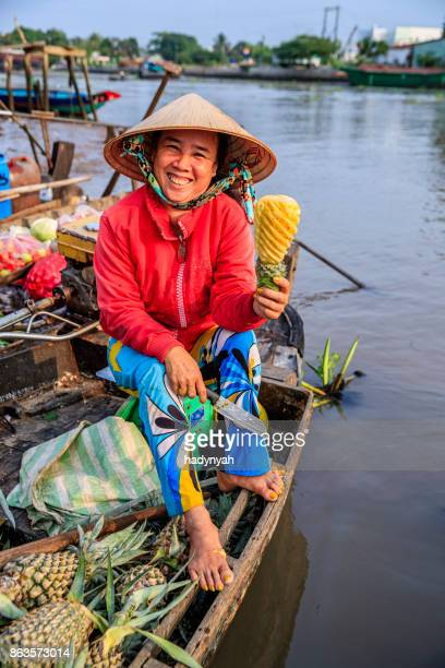 vietnamese woman selling pineapples on floating market, mekong river delta, vietnam - can tho province stock pictures, royalty-free photos & images