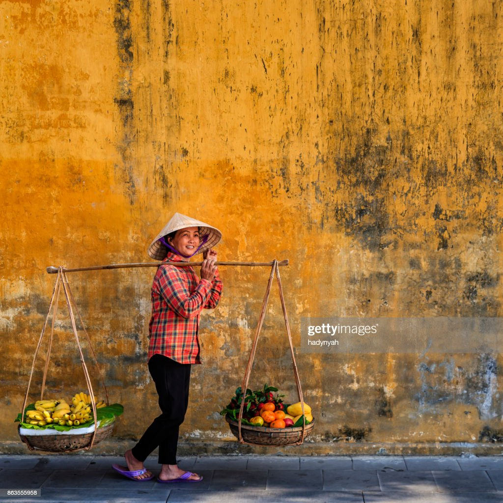 Vietnamese woman selling tropical fruits, old town in Hoi An city, Vietnam : Stock Photo