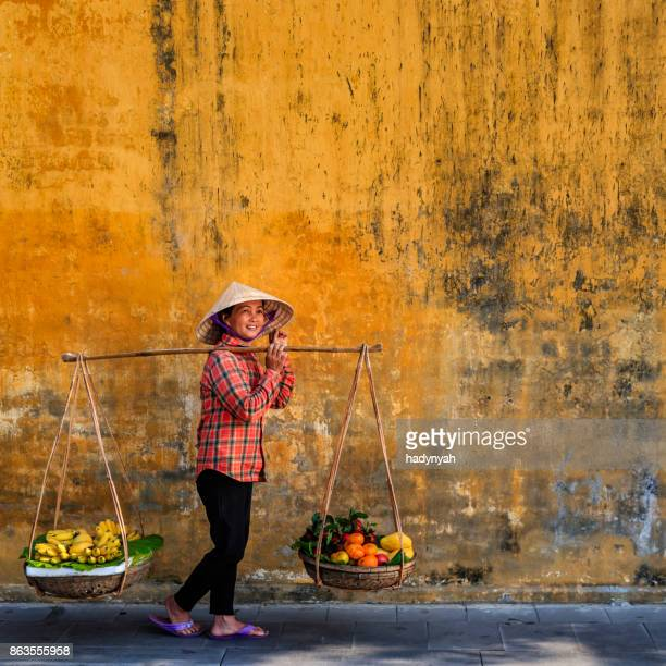 vietnamese woman selling tropical fruits, old town in hoi an city, vietnam - yellow hat stock pictures, royalty-free photos & images