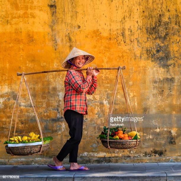 donna vietnamita che vende frutta tropicale, città vecchia nella città di hoi an, vietnam - cultura vietnamita foto e immagini stock