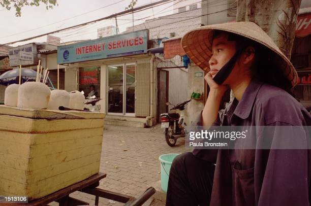 Vietnamese woman sells coconuts and waits for business outside a local internet center November 19 2000 in Ho Chi Minh City Vietnam