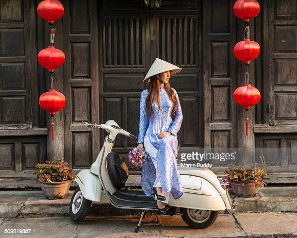 Vietnamese woman sitting on vespa on street side