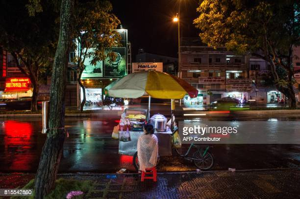 Vietnamese woman tending to a street car where she sells corn sits on a stool as she waits for customers after a storm in the southern city of Can...