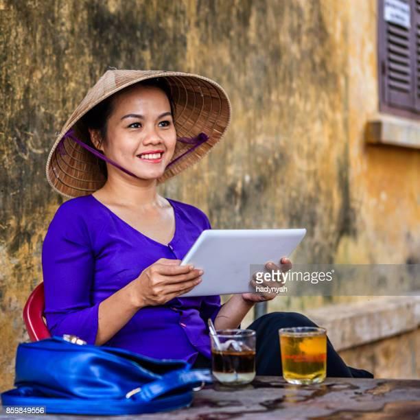 Femme vietnamienne à l'aide de tablette numérique au cours de la pause café, vieille ville de Hoi An ville, Vietnam