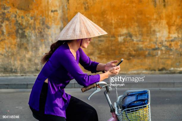 vietnamese woman using mobile phone on a bicycle, old town in hoi an city, vietnam - vietnamese culture stock pictures, royalty-free photos & images