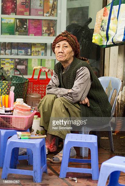 Vietnamese woman waits for customers at a roadside tea stall in Hanoi's Hoan Kiem district in the Old Quarter. March 2013