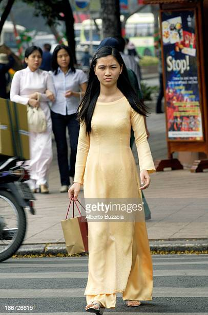 Vietnamese woman walking on the streets of Saigon wearing the traditional Ao Dai Ao Dai are seen more and more rarely as young generations of...