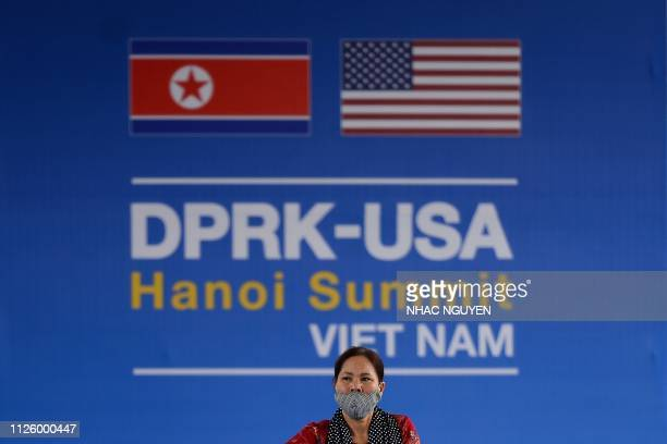 A Vietnamese woman walks past a billboard for the upcoming second summit between US President Donald Trump and North Korean leader Kim Jong Un in...