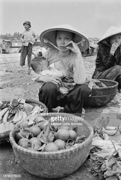 Vietnamese woman, wearing a traditional non la hat, holds her baby in her arm as she sells vegetable from a basket on an embankment of the Saigon...